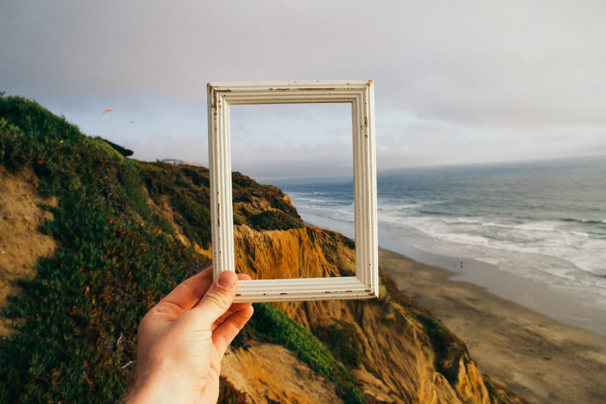 hand holding empty picture frame to ocean scene