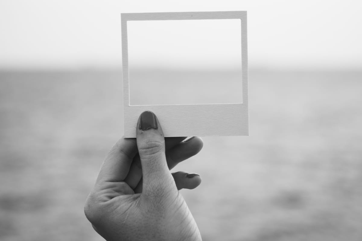 hand holding empty photo frame in landscape